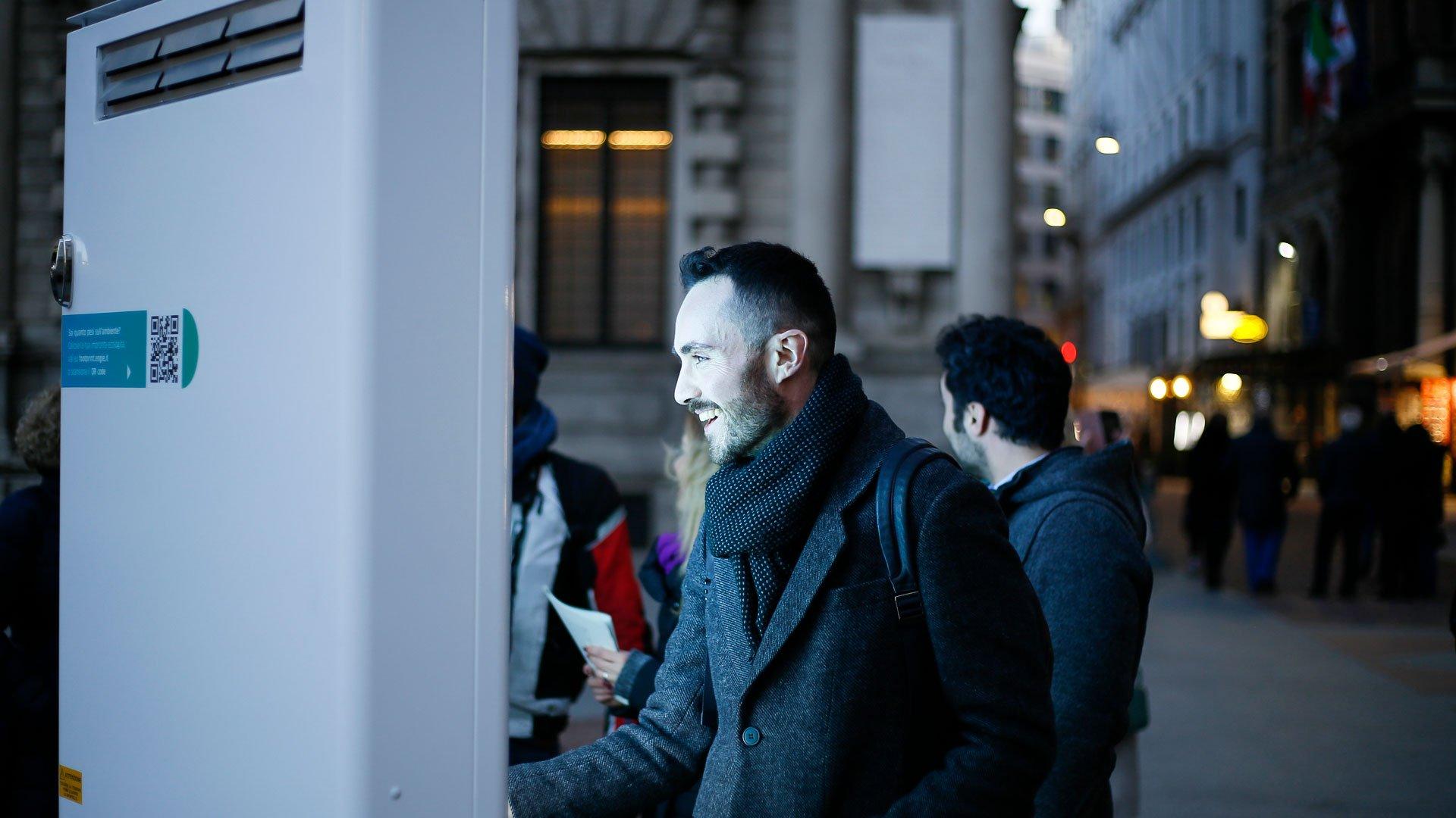 uomo sorridente davanti a totem interattivo